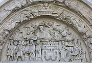 Martyrdom of St Denis, with St Denis, Rustique and Eleuthera led away in chains for their beliefs, relief on the tympanum of the North portal of the West facade, made 1135 and restored in 1839, at the Basilique Saint-Denis, Paris, France. Abbot Suger originally had a mosaic made on this tympanum, and was introducing a hagiography of St Denis with this imagery. The basilica is a large medieval 12th century Gothic abbey church and burial site of French kings from 10th - 18th centuries. Picture by Manuel Cohen