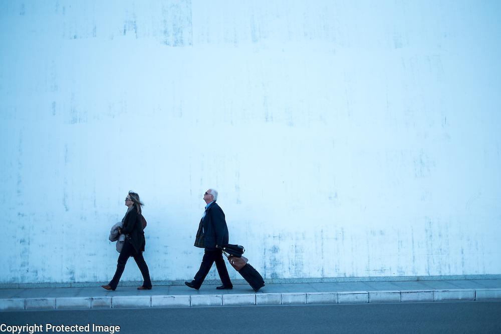 A couple carry their bags along Ave Princesse Grace in Monte Carlo, Monaco.