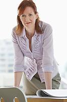 Woman leaning on desk in office portrait