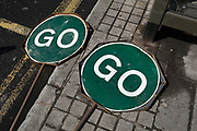 Two GO traffic road signs lie by the road in East Dulwich, on 26th April 2018, in London, England.