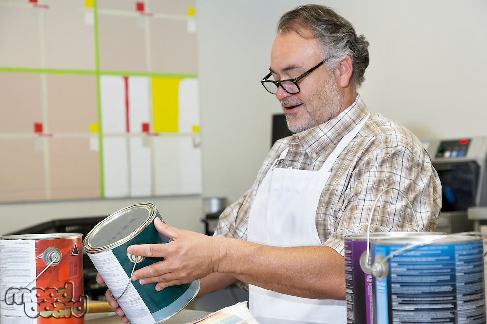 Happy mature sales clerk reading instructions paint can in hardware store