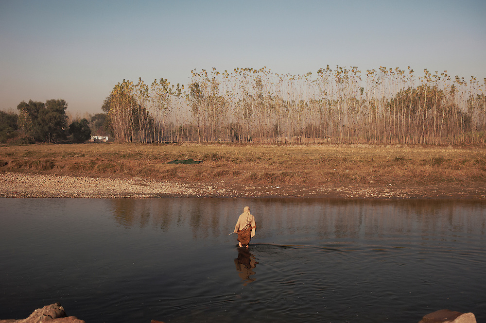 Pakistan/ Afghan refugees/ A women wades through a river in the Khazana refugee camp, Peshawar. The camp was established when refugees flooded across the border from Afghanistan during the 1979 Soviet occupation. The refugee camp has a population of 2500 and during the 2010 floods that swept through Pakistan most families were affected. The majority of people rebuilt their houses after the floods with their own resources. The most vulnerable also received support from UNHCR for reconstruction. UNHCR/Sam Phelps/ November 2011.