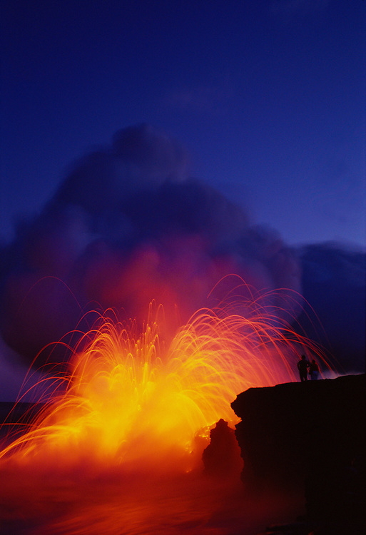 Couple watching lava explode as flow from Pu'u O'o eruption hits ocean; Hawaii Volcanoes National Park.