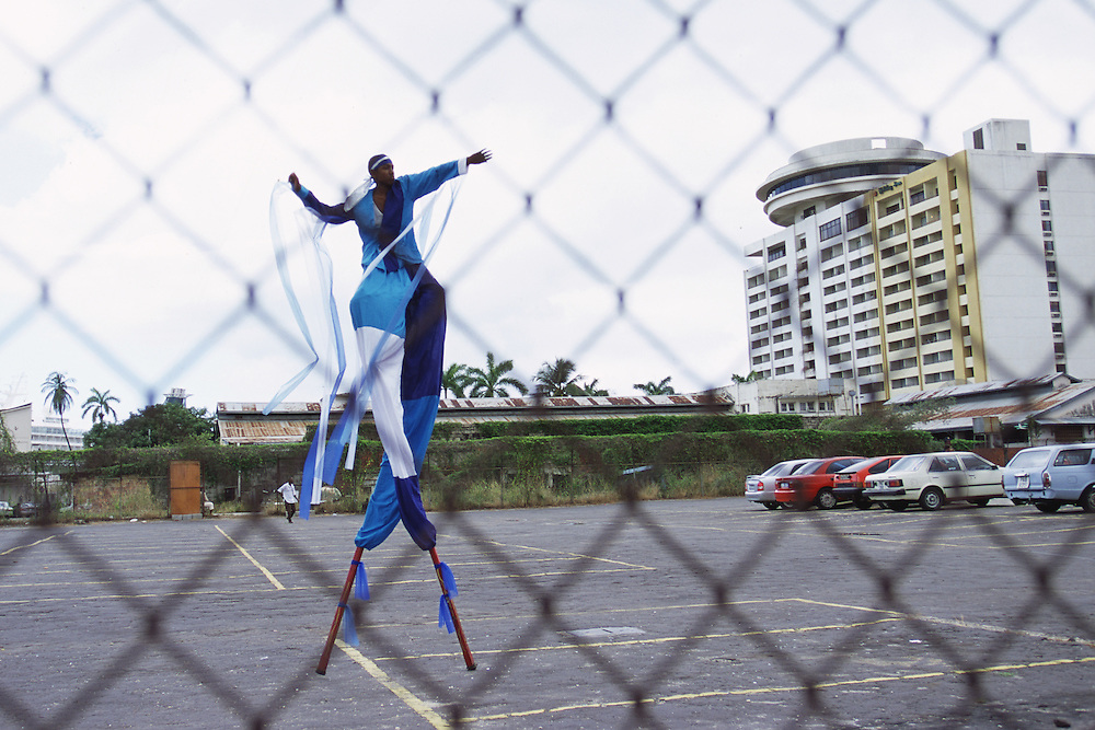"""Trinidad and Tobago """"MOKO JUMBIES: The Dancing Spirits of Trinidad"""".(Akeil Jacob in the open space of the parking lot on Richmond Street in Port of Spain).A photo essay about a stilt walking school in Cocorite, Trinidad..Dragon Glen de Souza founded the Keylemanjahro School of Art & Culture in 1986. The main purpose of the school is to keep children off the streets and away from drugs..He first taught dances like the Calypso, African dance and the jig with his former partner Cathy Ann Samuel.  Searching for other activities to engage the children in, he rediscovered the art of stilt-walking, a tradition known in West Africa as the Moko Jumbies , protectors of the villages and participants in religious ceremonies. The art was brought to Trinidad by the slave trade and soon forgotten..Today Dragon's school has over 100 members from age 4 and up..His 2 year old son Mutawakkil is probably the youngest Moko Jumbie ever. The stilts are made by Dragon and his students and can be as high as 12-15 feet. The children show their artistic talents mostly at the annual Carnival, which today is unthinkable without the presence of the Moko Jumbies. A band can have up to 80 children on stilts and they have won many of the prestigious prizes and trophies that are awarded by the National Carnival Commission. Designers like  Peter Minshall , Brian Mac Farlane and Laura Anderson Barbata create dazzling costumes for the school which are admired by thousands of  spectators. Besides stilt-walking the children learn the limbo dance, drumming, fire blowing and how to ride  unicycles..The school is situated in Cocorite, a suburb of Port of Spain, the capital of Trinidad and Tobago..all images © Stefan Falke"""