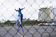 "Trinidad and Tobago ""MOKO JUMBIES: The Dancing Spirits of Trinidad"".(Akeil Jacob in the open space of the parking lot on Richmond Street in Port of Spain).A photo essay about a stilt walking school in Cocorite, Trinidad..Dragon Glen de Souza founded the Keylemanjahro School of Art & Culture in 1986. The main purpose of the school is to keep children off the streets and away from drugs..He first taught dances like the Calypso, African dance and the jig with his former partner Cathy Ann Samuel.  Searching for other activities to engage the children in, he rediscovered the art of stilt-walking, a tradition known in West Africa as the Moko Jumbies , protectors of the villages and participants in religious ceremonies. The art was brought to Trinidad by the slave trade and soon forgotten..Today Dragon's school has over 100 members from age 4 and up..His 2 year old son Mutawakkil is probably the youngest Moko Jumbie ever. The stilts are made by Dragon and his students and can be as high as 12-15 feet. The children show their artistic talents mostly at the annual Carnival, which today is unthinkable without the presence of the Moko Jumbies. A band can have up to 80 children on stilts and they have won many of the prestigious prizes and trophies that are awarded by the National Carnival Commission. Designers like  Peter Minshall , Brian Mac Farlane and Laura Anderson Barbata create dazzling costumes for the school which are admired by thousands of  spectators. Besides stilt-walking the children learn the limbo dance, drumming, fire blowing and how to ride  unicycles..The school is situated in Cocorite, a suburb of Port of Spain, the capital of Trinidad and Tobago..all images © Stefan Falke"