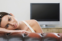 Young woman on sofa in front of flat screen television portrait
