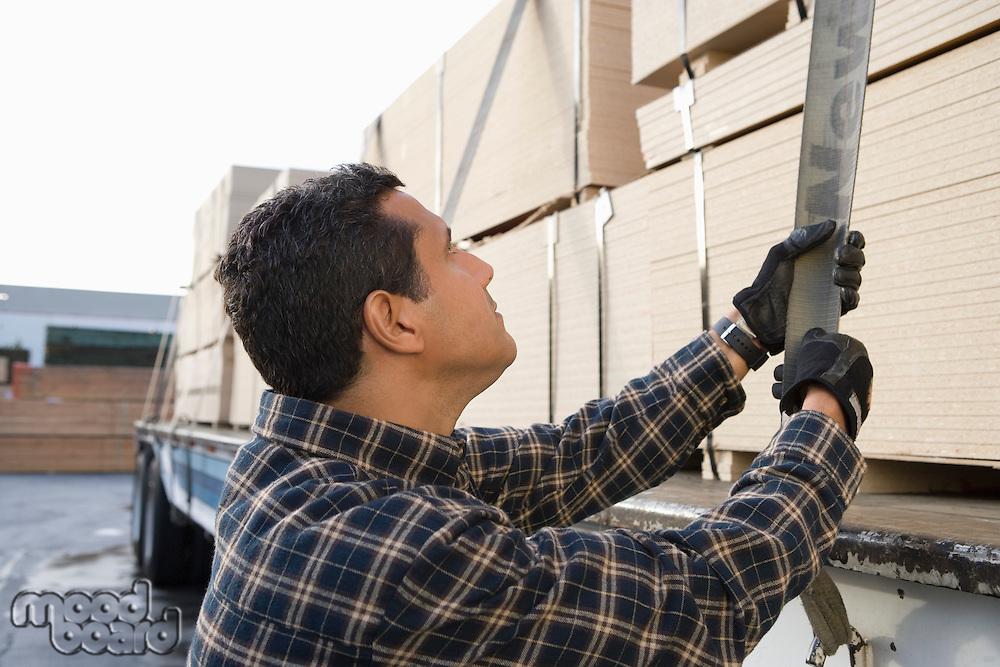 Mid-adult man checking strapping of truck loaded with wood