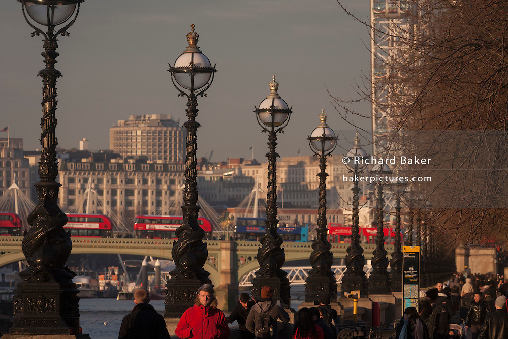 Crowds walk along The Queen's Walk on the south bank of the River Thames, with the London Eye and buses crossing Westminster Bridge, on 18th January 2017, in London England.