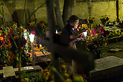 An elderly woman holds a candle at the gravesite of a relative at Xoxocatian cemetery decorated with flowers and candles for the Day of the Dead Festival known in spanish as Día de Muertos on October 31, 2014 in Oaxaca, Mexico.