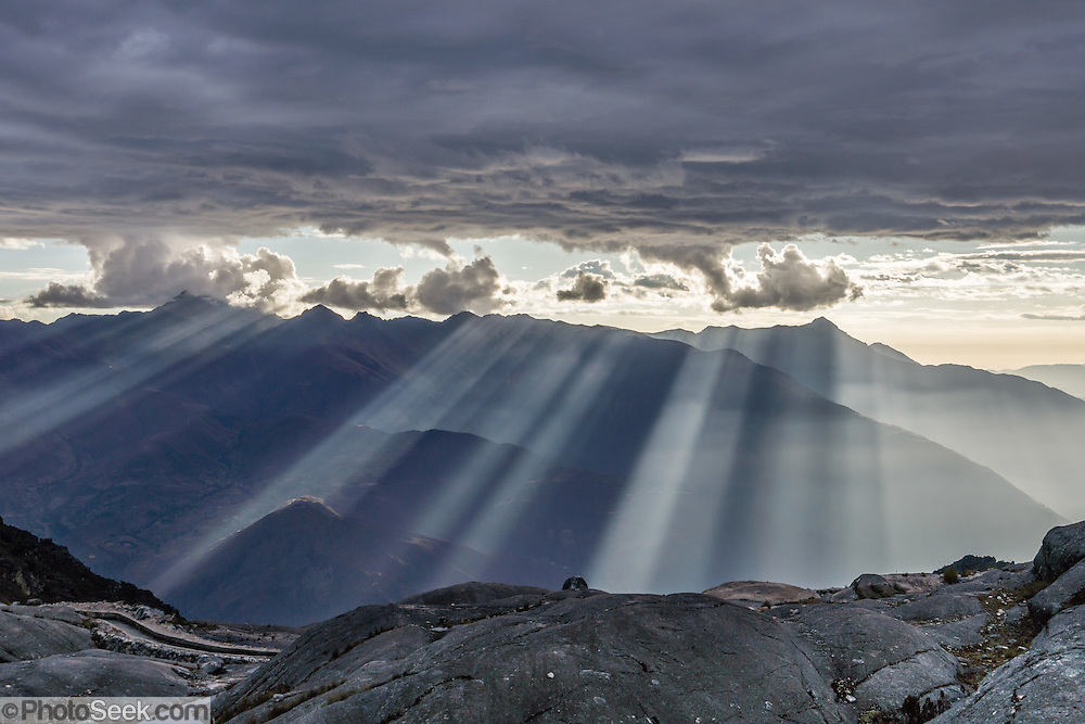 Spectacular rays of afternoon light pierce clouds over the Cordillera Negra and spotlight the Santa Valley (historically known as Callejon de Huaylas/Alley of Huaylas) in the Ancash Region in the north-central highlands of Peru. The viewpoint is from Lake Cullicocha, high above Hualcayan village. This was day 8 of 10 days trekking around Alpamayo in Huascaran National Park (UNESCO World Heritage Site), Cordillera Blanca, Andes Mountains, Peru, South America.