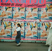 Woman and child walking past a wall covered with posters advertising Karisma Kapoor and Daler Mehndi 'The dynamic duo' Sunday 25th June at Wembley Arena