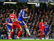 Cesc Fabregas of Chelsea (centre) heads the ball ahead of Philippe Coutinho of Liverpool (left) during the Capital One Cup Semi Final 2nd Leg match between Chelsea and Liverpool at Stamford Bridge, London, England on 27 January 2015. Photo by David Horn.