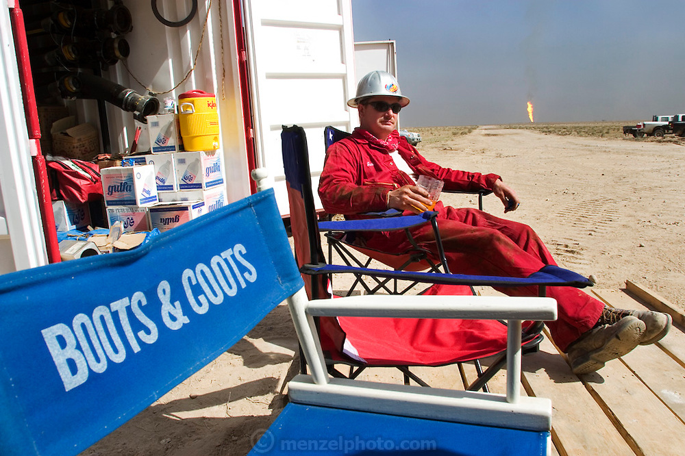 Gari of Boots and Coots takes a mid-morning break in front of one of the equipment containers near a raging oil well fire in Rumaila field, Southern Iraq. Another fire blazes in the distance. The Rumaila field is one of Iraq's biggest with five billion barrels in reserve. Boots and Coots had a team of firefighters in Kuwait ready to go into Iraq several weeks before the war began. All of their equipment (including bulldozers and trucks) was flown in from Texas on large Russian cargo planes (AN-124s). Rumaila is also spelled Rumeilah.