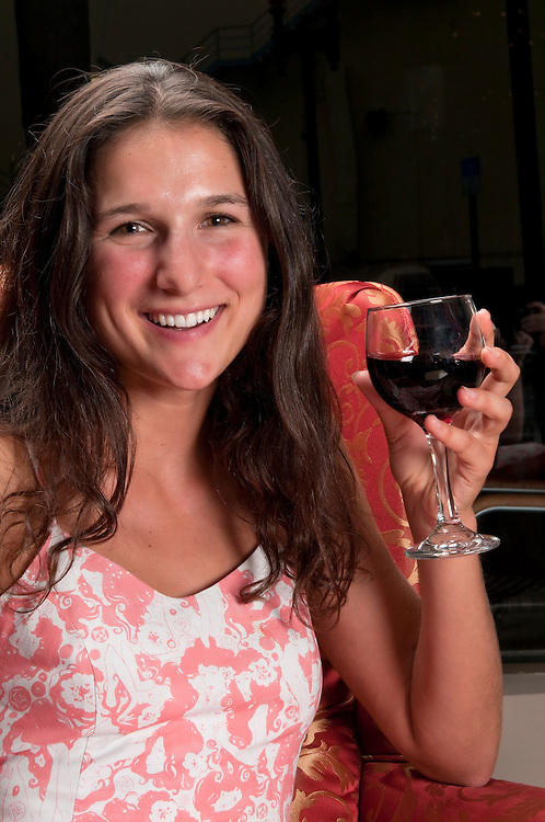 Young woman very happy drinking wine in a restaurant.