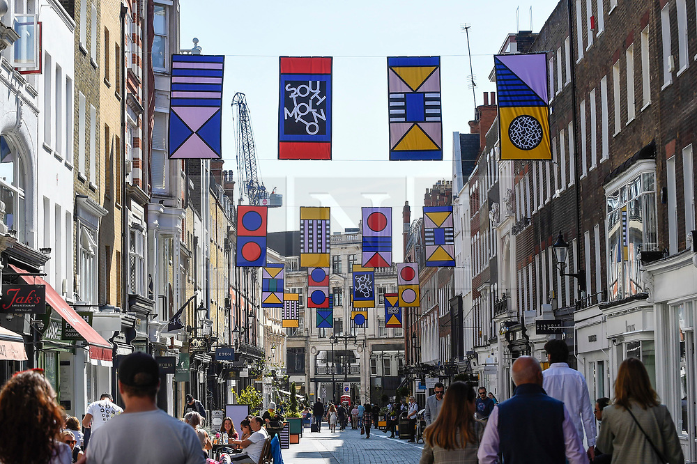 """© Licensed to London News Pictures. 14/09/2019. LONDON, UK.  The """"Walala Lounge"""" opens in Mayfair's South Molton Street.  Artist and designer Camille Walala's installation comprises 10 sculptural benches, accompanied by planters and a series of oversized flags strung, bunting-style, from shopfront to shopfront, converting the street into an immersive corridor of colour as part of this year's London Design Festival.  Photo credit: Stephen Chung/LNP"""