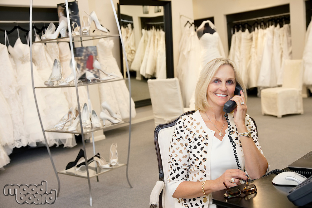 Portrait of a happy woman making a call in bridal store