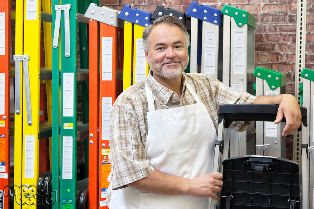 Portrait of happy mature store clerk standing by multicolored ladders in hardware shop