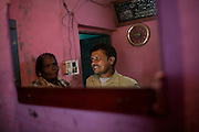 Shafiq Syed, 34, is portrayed on a mirror with his mother inside her home in the poor Bangalore neighbourhood where he now also lives with his family. Shaifq has been the main character of the Cannes' Camera D'Or 1988 winner Salaam Bombay, but after the movie he failed to become a star, fell back into poverty and lived on the streets for years before he became a rickshaw (tuk-tuk) driver in his home city of Bangalore, Karnataka State, India.