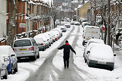 © Licensed to London News Pictures. 21/01/2013, London, UK. A man steady himself as he walks down a snow covered street in Croydon, South London, Monday, Jan. 21, 2013. Britain is continue affect by cold weather and snow. Photo credit : Sang Tan/LNP