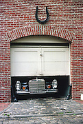 Mercedes car with front protruding under partially closed small garage door; brick wall; cobblestones. tight fi