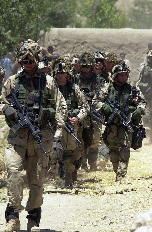 U.S. Army soldiers from the 101st Airborne move through the eastern Afghan village of Hesarak on July 16, 2002 during what the Army refers to as a 'sensitive site exploitation' mission or 'SSE'. The army says that Hesarak was raided for the first time four days ago when undisclosed intelligence materials were gathered. Today's raid was intended both to search for more materials and to provide some hunanitarian aid to local residents.