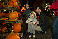 Jayden Fiore, Landon LaPierre and Ethan Anderson pick out their favorite pumpkins from the racks along Main Street during Pumpkin Fest Saturday evening.  (Karen Bobotas/for the Laconia Daily Sun)