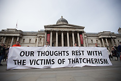 "© Licensed to London News Pictures . 17/04/2013 . London , UK . Protesters from The National Union of Rail, Maritime and Transport Workers ( RMT ) unfurl a banner reading "" Our thoughts rest with the victims of Thatcherism "" in Trafalgar Square . The funeral of former British Conservative Prime Minister , Baroness Margaret Thatcher , today (Wednesday 17th April 2013) in Central London . Baroness Thatcher died from a stroke at the age of 87 . Photo credit : Joel Goodman/LNP"