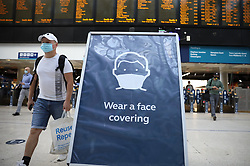 © Licensed to London News Pictures. 15/06/2020. London, UK. A sign asks passengers to wear face masks as they arrive at Waterloo Station. New rules allowing some non-essential retail businneses to open and mandatory face masks on public transport have started today. Photo credit: Peter Macdiarmid/LNP
