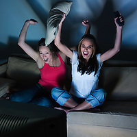 pictures in a living room of two young girls sitting on a couch watching on tv sport event