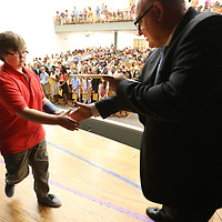 Milam student Dylan Whitehead, reaches out to shake hands with his teacher, Joe Benefield, as he receives his awards during the promotion ceremony at Milam Thursday morning in Tupelo.