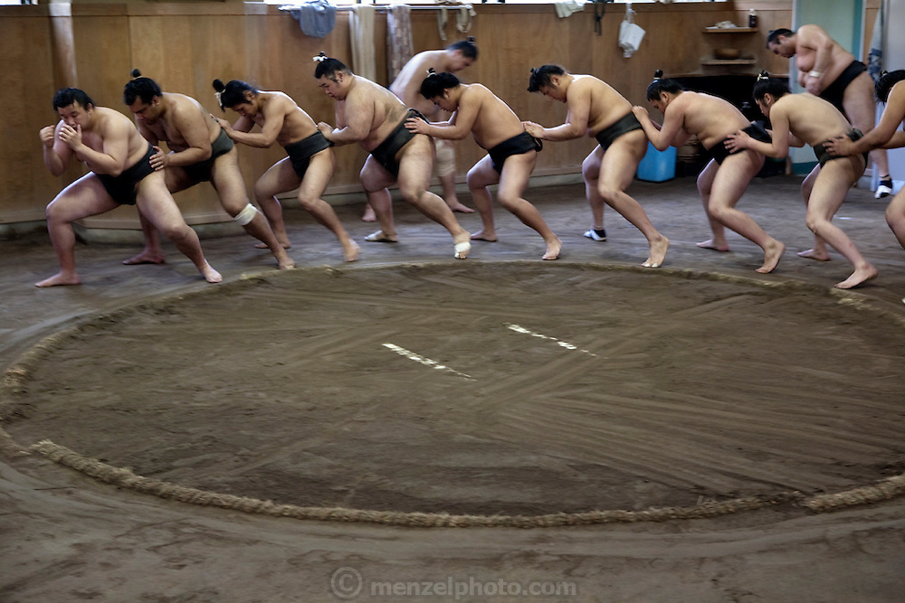 Wrestlers of the Professional Sumo Team (Musahigawa Beya) go through practice routines at their stable in Tokyo, Japan. Younger, smaller, and less experienced sumo wrestlers go through exercises emphasizing team unity at the end of a grueling morning practice. (From the book What I Eat: Around the World in 80 Diets.)