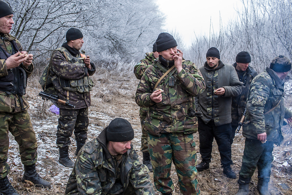 ARTEMIVSK, UKRAINE - FEBRUARY 15: Ukrainian soldiers eat sausage cooked over a fire along the road leading to the embattled town of Debaltseve on February 15, 2015 outside Artemivsk, Ukraine. A ceasefire scheduled to go into effect at midnight was reportedly observed along most of the front, save for near the embattled town of Debaltseve. (Photo by Brendan Hoffman/Getty Images) *** Local Caption ***