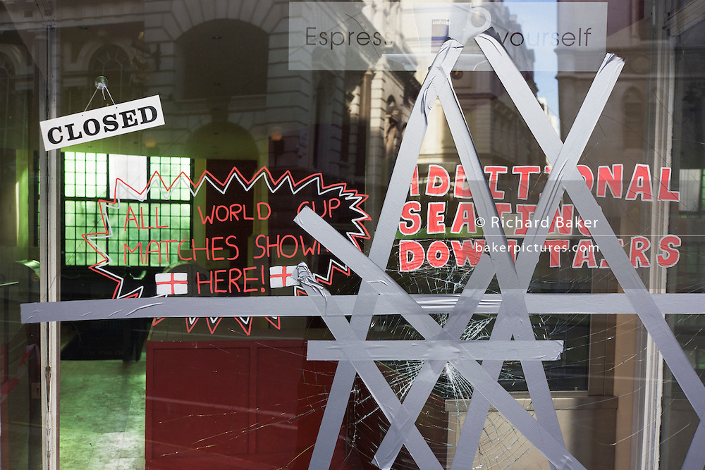A closed cafe with taped, cracked glass on Fleet Street, City of London a victim of the UK recession.