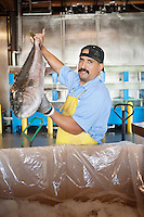 Portrait of mature fishmonger holding salmon fish