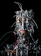 The inner workings of the first generation face robot from the Hara-Kobayashi Lab in Tokyo, Japan. The first of several face robots made in Fumio Hara's lab, it has a CCD camera in its left eye that sends images to neural-network software that recognizes faces and their expressions. Calling upon its repertoire of programmed reactions, it activates the motors and pulleys beneath its flexible skin to produce facial expressions of its own. From the book Robo sapiens: Evolution of a New Species, page 4.