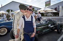 **CAPTION CORRECTION. Picture originally sent with wrong date. Picture was taken TODAY 11/09/2015** © licensed to London News Pictures. 11/09/2015<br /> Goodwood Revival Weekend, Goodwood, West Sussex. UK.<br /> The Goodwood Revival is the world's largest historic motor racing event. Competitors and enthusiasts dress in period fashions recreating the glorious days of the race circuit.<br /> Pictured Driver Burkhard List and his wife and mechanic Michaela kiss in front of their 1935 Frazernash.<br /> <br /> Photo credit : Ian Whittaker/LNP