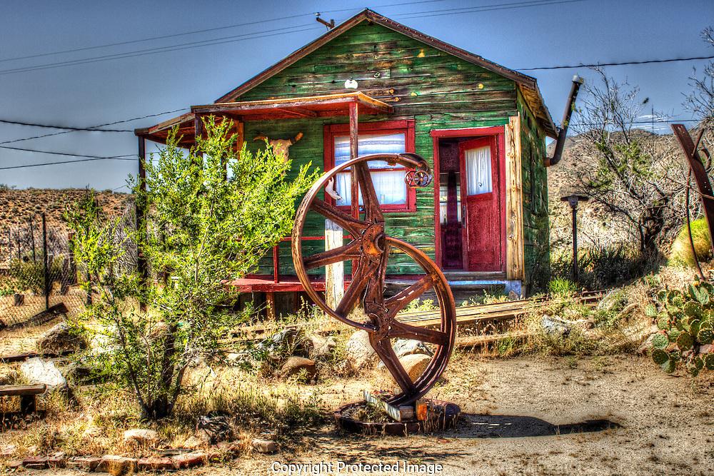 Mine cart rails run between junk yard art and miner's shack in Chloride, Arizona