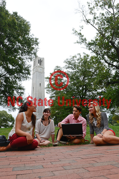Students talk at the Belltower on campus. Photo by Marc Hall