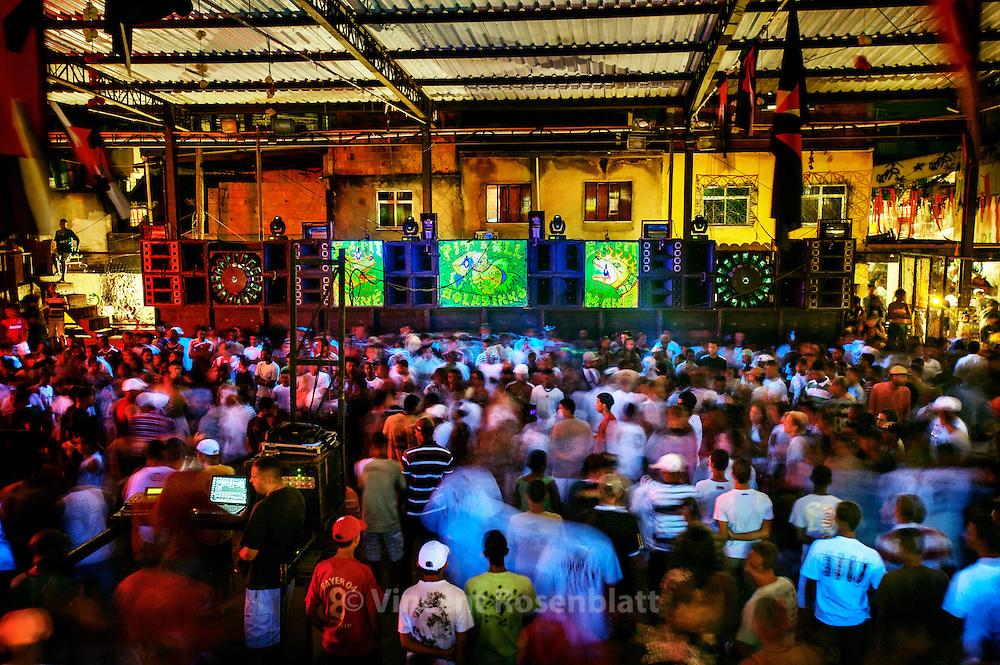 "Mythical ball in the  favela Chatuba, Complexo da Penha. The favela  Chatuba is famous for having resisted to the assault of the Military Police for weeks in 2008, and was finally occupied by the Brazilian Army at the end of 2010. it also hosted one of the most famous and crowded bailes funk of Rio de Janeiro. As a song says, it's the ""Maracanã of Funk"", comparing the  Baile to the city's biggest football stadium.   Here with the Pitbull soundsystem that runs the baile toguether with the  ""Chatubão Digital"" soundsystem.      ||           Baile mythique de la favela de Chatuba, Complexo da Penha. Connues pour avoir résisté des semaines victorieusement aux assauts de la police militaire en 2008, la favela de Chatuba est occupée par l'armée brésilienne depuis fin 2010. Elle abritait aussi un des plus connu et bondé des Bailes Funk de Rio de Janeiro. Comme dit une musique, c'est le ""Maracanã do Funk"", comparant le Baile au plus grand stade de foot de la ville, et d'Amérique Latine. L'equipe de don Pitbull se partage le Baile avec l'équipe locale, le ""Chatubão Digital""."