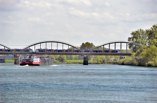 Nederland, Batenburg, Ravenstein, 8-5-2018 De oude enkelspoors spoorbrug ovber de Maas . De Maas krijgt de ruimte. Door de aanleg van natuurvriendelijke oevers ontstaat er een geleidelijke overgang van water naar land. Op veel plaatsen langs de meanderende maas zijn nevengeulen aangelegd om het water meer ruimte tegeven . Het talud van de spoorbrug vormt een obstakel bij hoogwater .Foto: Flip Franssen