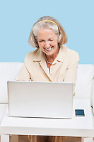 Cheerful senior woman using laptop for video calling
