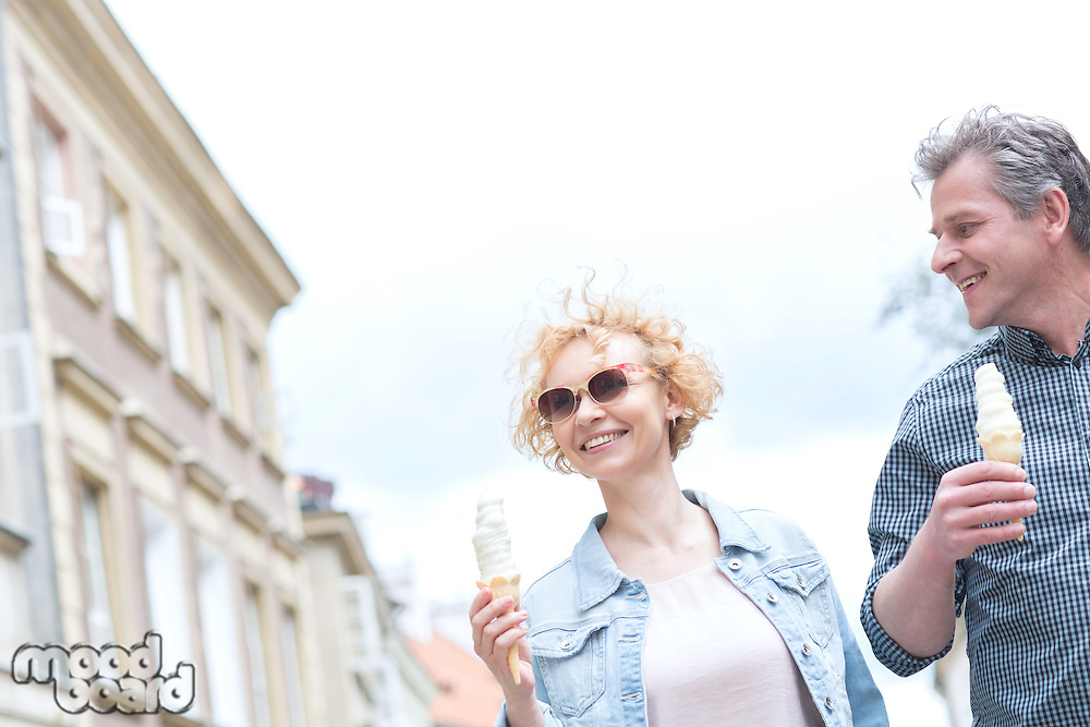 Smiling middle-aged couple holding ice cream cones on sunny day