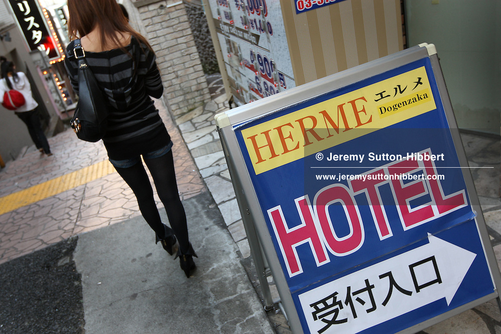 A young woman waits for her client outside the Hotel Herme in the Love hotels district, in the hillside streets of Shibuya district, Tokyo, Japan, Monday 22nd Oct, 2007.