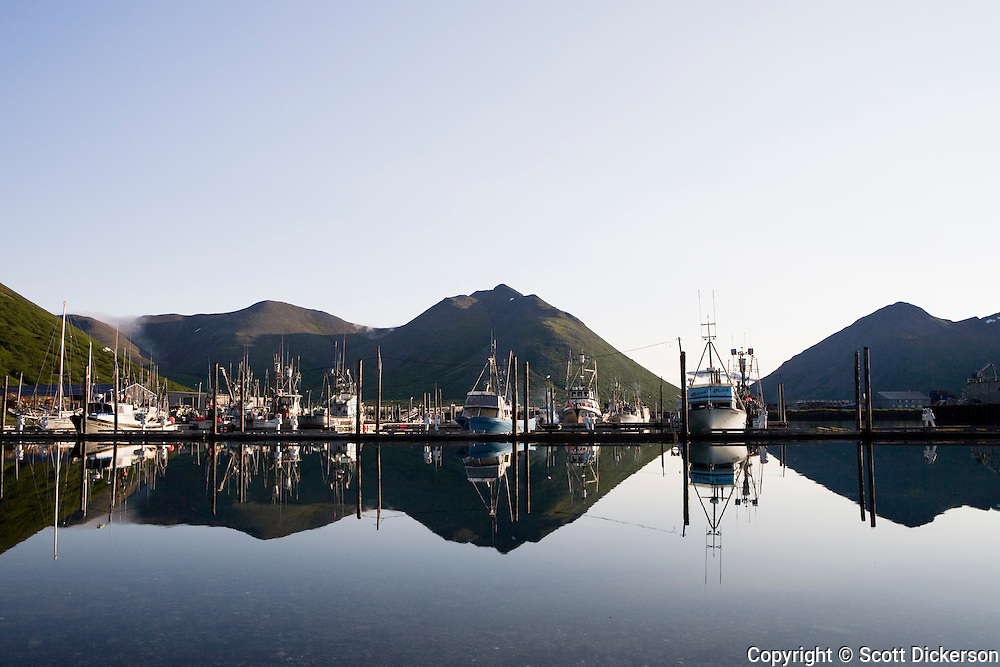 The fishing boats and mountains in the light of dawn refelect in the still waters of the King Cove harbor, King Cove, Alaska Peninsula, Alaska.