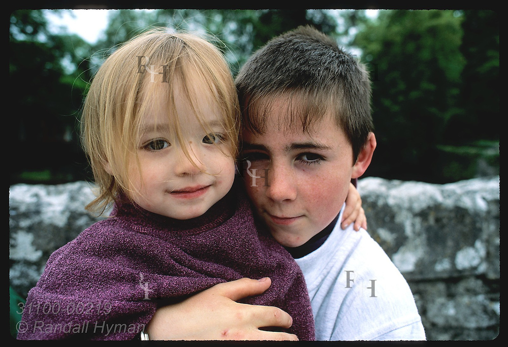 Boy holds up little girl cousin for picture in village of Cong.  Ireland