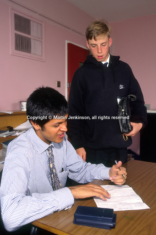 New Teacher in his first year completing a pupils report sheet  in a Secondary School...© Martin Jenkinson tel 0114 258 6808  mobile 07831 189363 email martin@pressphotos.co.uk  NUJ recommended terms & conditions apply. Copyright Designs & Patents Act 1988. Moral rights asserted credit required. No part of this photo to be stored, reproduced, manipulated or transmitted by any means without prior written permission.