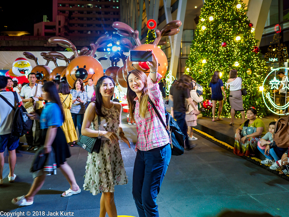 """23 NOVEMBER 2018 - BANGKOK, THAILAND:  Woman take """"selfies"""", in the """"World of Happiness,"""" the Christmas display at Central World, a large mall in Bangkok. Although Thailand is an overwhelmingly Buddhist country, the commercial aspects of Christmas are widely observed, especially in Thailand's urban areas, which have large concentrations of Europeans and Americans.    PHOTO BY JACK KURTZ"""