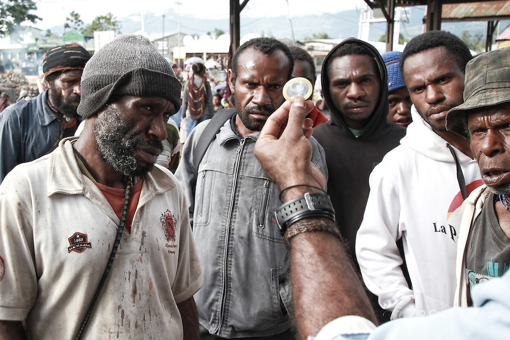 A member of YPKM, a local NGO, demonstrates the use of a condom during an HIV and STD awareness raising campaign at a local market. These kind of campaigns are still very rare.
