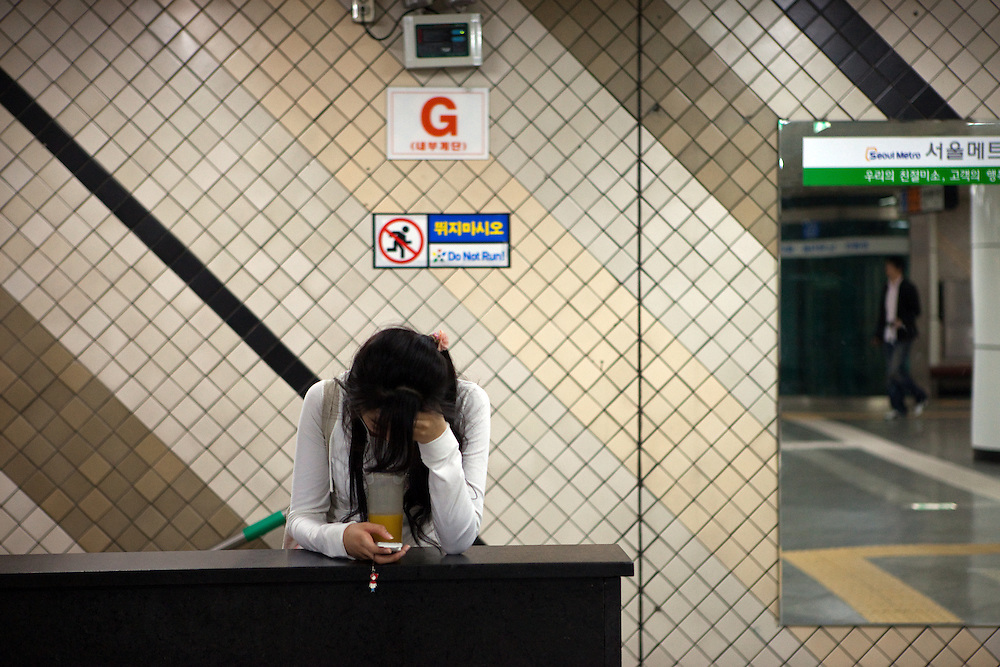 Junge Frau wartet mit einem Orangensaft und ihrem Mobil Telefon an einer Station der Seoul Metro. <br /> <br /> Young woman with orange juice and mobile phone is waiting at a Seoul Metro station.