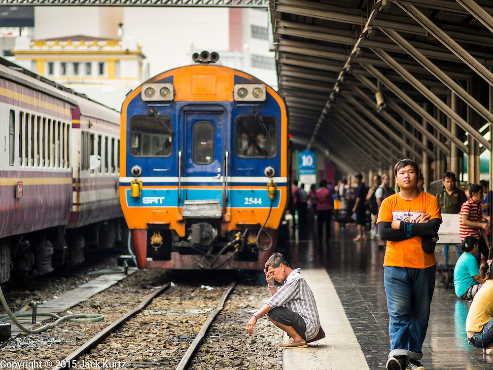 19 MARCH 2015 - BANGKOK, THAILAND:   A man smokes a cigarette while he waits for a train to leave Hua Lamphong Train Station in Bangkok. The State Railways of Thailand (SRT), established in 1890, operates 4,043 kilometers of meter gauge track that reaches most parts of Thailand. Much of the track and many of the trains are poorly maintained and trains frequently run late. Accidents and mishaps are also commonplace. Successive governments, including the current military government, have promised to upgrade rail services. The military government has signed contracts with China to upgrade rail lines and bring high speed rail to Thailand. Japan has also expressed an interest in working on the Thai train system. Third class train travel is very inexpensive. Many lines are free for Thai citizens and even lines that aren't free are only a few Baht. Many third class tickets are under the equivalent of a dollar. Third class cars are not air-conditioned.      PHOTO BY JACK KURTZ